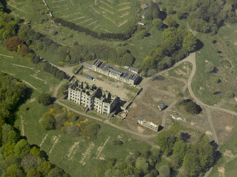 Oblique aerial view centred on the ruins of the country house, taken from the ENE.
