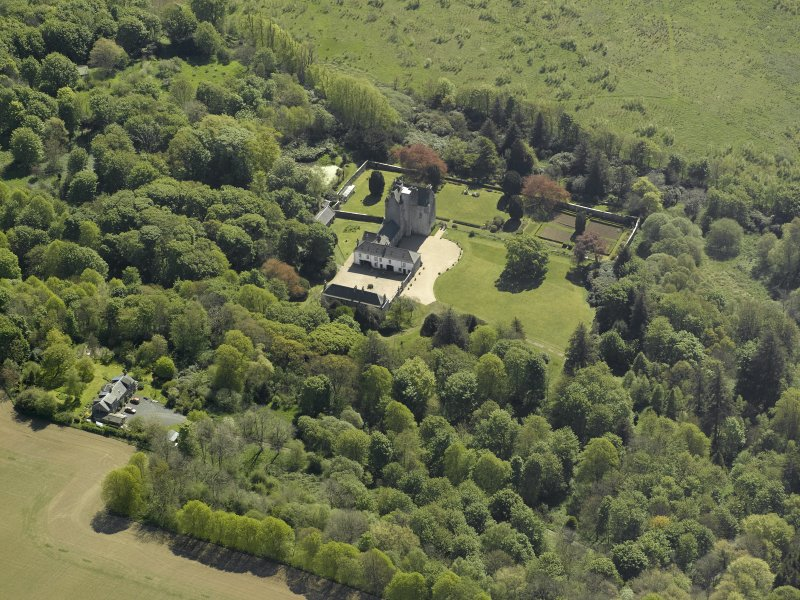Oblique aerial view centred on the castle and country house,  taken from the NW.