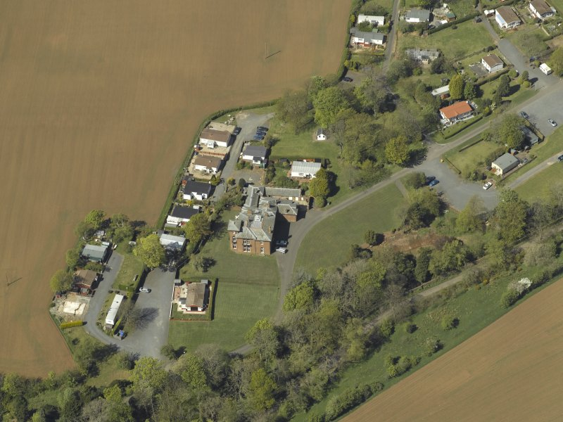 General oblique aerial view centred on the house with caravan park adjacent, taken from the SE.