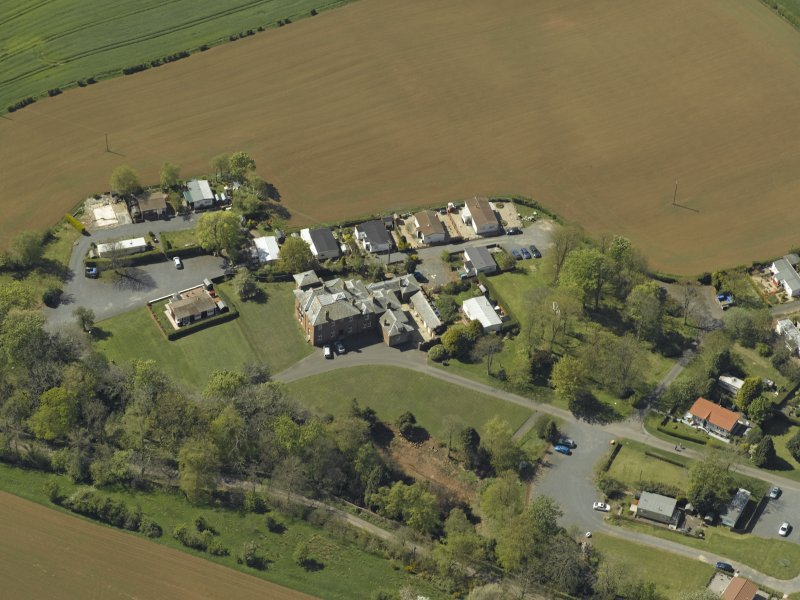 General oblique aerial view centred on the house with caravan park adjacent, taken from the NE.