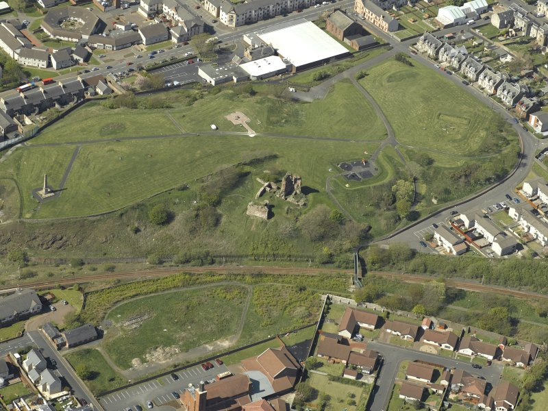 Oblique aerial view centre on the remains of Ardrossan Castle with the Monument adjacent, taken from the SE.