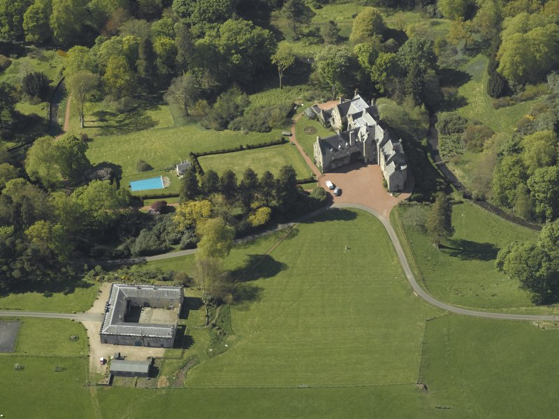 Oblique aerial view centred on the house with the stable block adjacent, taken from the SE.