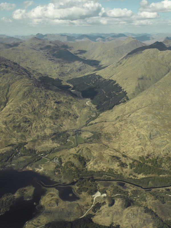Oblique aerial view looking towards Glen Finnan centred on the Glenfinnan railway viaduct with the Glenfinnan Monument adjacent, view from SSW.