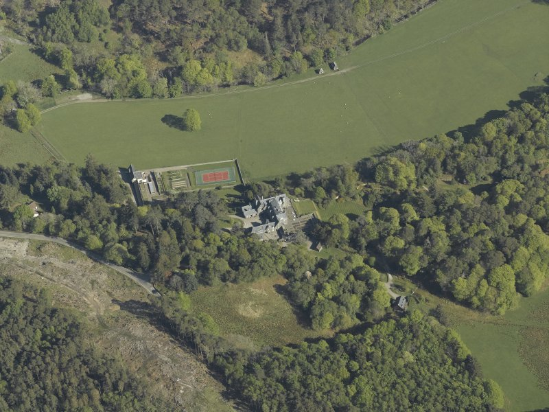 Oblique aerial view centred on the house with the gardener's cottage and walled garden adjacent, taken from the SSE.