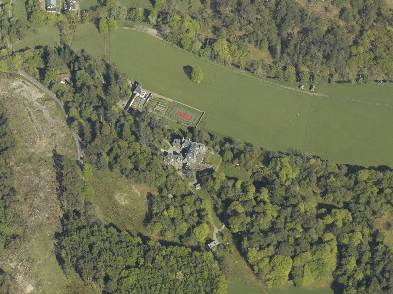 Oblique aerial view centred on the house with the gardener's cottage and walled garden adjacent, taken from the SW.