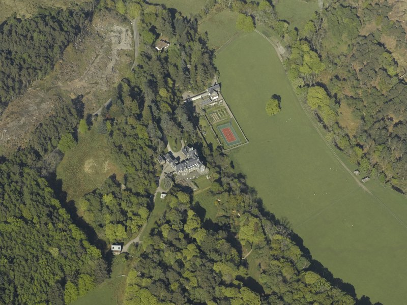 Oblique aerial view centred on the house with the gardener's cottage and walled garden adjacent, taken from the W.