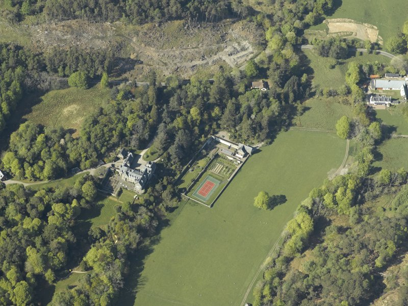 Oblique aerial view centred on the house with the gardener's cottage and walled garden adjacent, taken from the WNW.