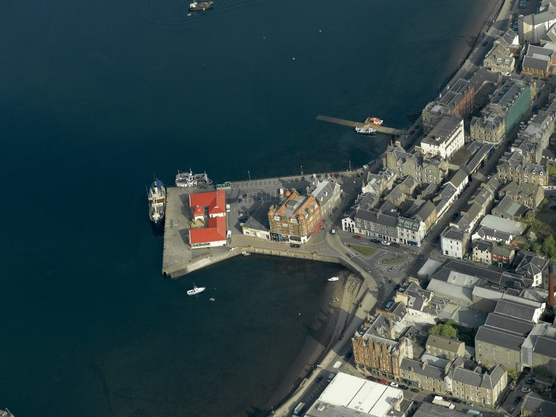 Oblique aerial view centred on the offices, pier and hotel, taken from the SW.