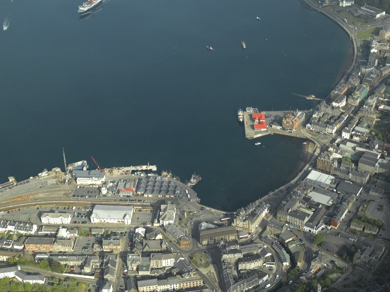 General oblique aerial view of the town centred on the railway station and the pier, taken from the SE.
