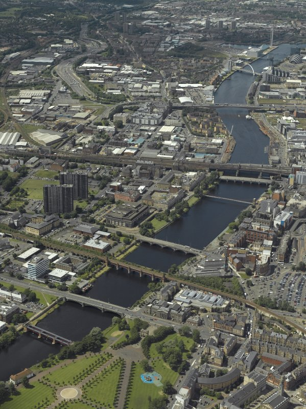 General oblique aerial view of Glasgow looking along the river, taken from the E.  View includes Millennium Bridge, Finnieston Bridge, Bell's Bridge, Central Station Viaduct, George the Fifth Bridge, Albert Bridge, Victoria Bridge, Union Railway Bridge, South Portland Street Suspension Footbridge, Glasgow Bridge and Kingston Bridge.