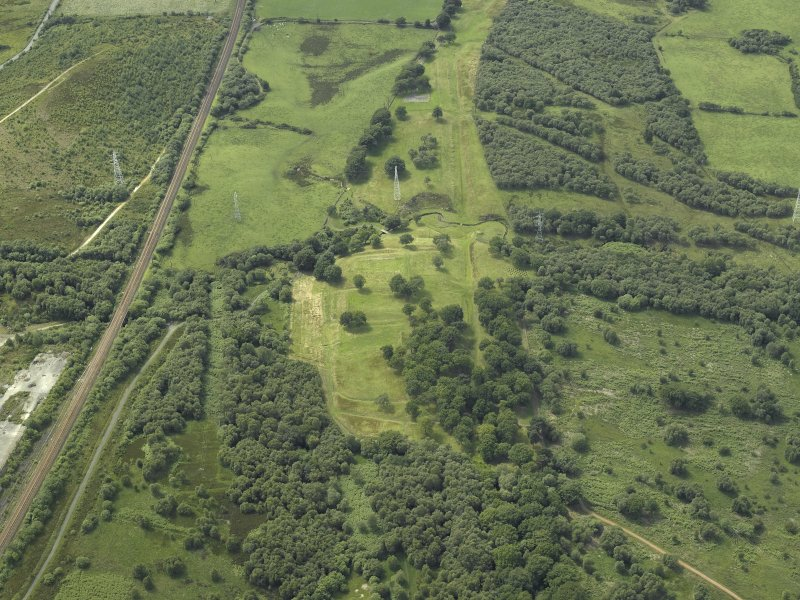 Gneral oblique aerial view centred on the remains of the Roman fort and the course of the Antonine Wall, taken from the E.