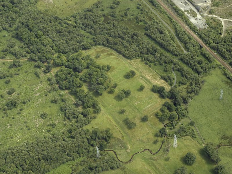 Oblique aerial view centred on the remains of the Roman fort and the course of the Antonine Wall, taken from the SSE.