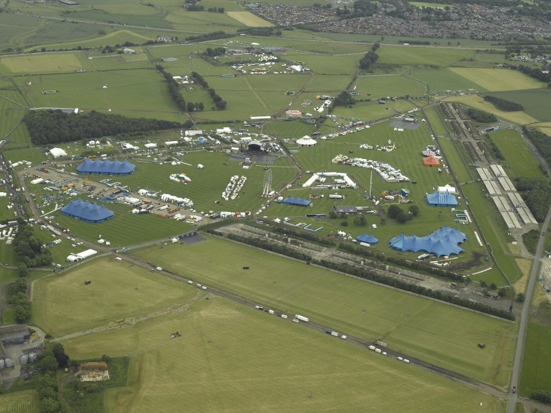 General oblique aerial view centred on the radio station and airfield with the aircraft hangars in the distance, taken during T in the Park from the W.