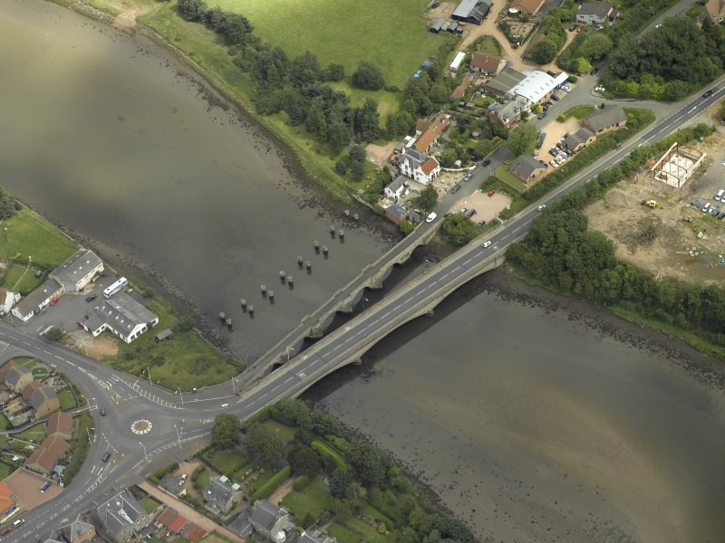 Oblique aerial view centred on the old bridge, rail bridge and new road bridge, taken from the SW.