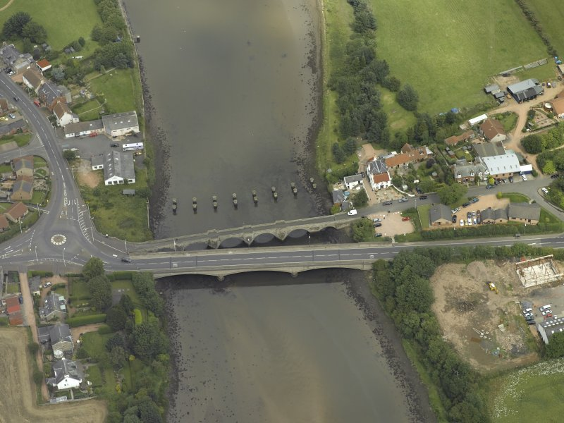 Oblique aerial view centred on the old bridge, rail bridge and new road bridge, taken from the SSE.