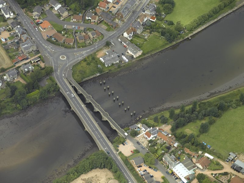 Oblique aerial view centred on the old bridge, rail bridge and new road bridge, taken from the SE.