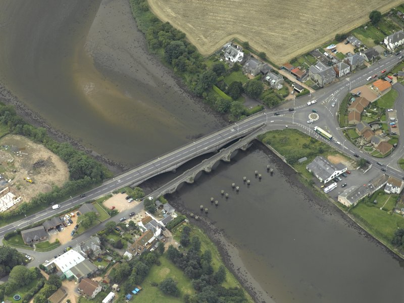 Oblique aerial view centred on the old bridge, rail bridge and new road bridge, taken from the NE.