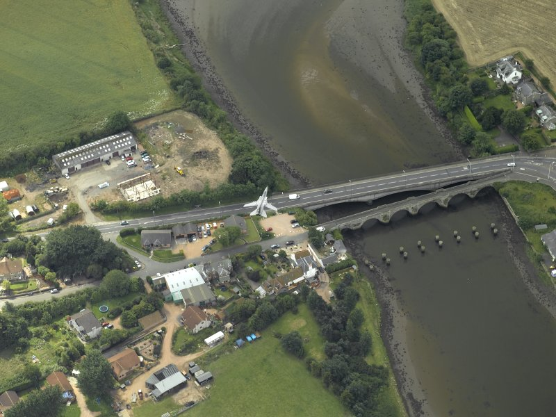 Oblique aerial view centred on the old bridge, rail bridge and new road bridge, with RAF Tornado passing, taken from the NE.