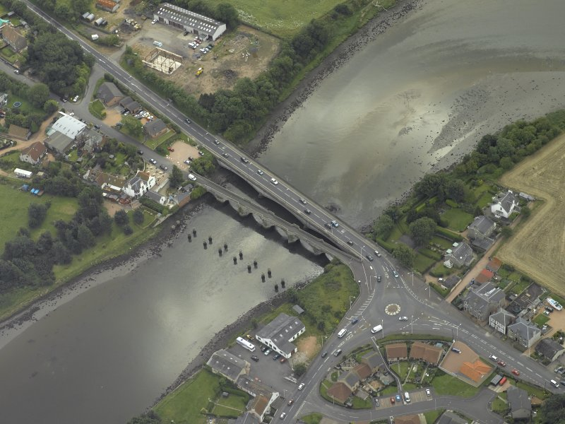 Oblique aerial view centred on the old bridge, rail bridge and new road bridge, taken from the NW.