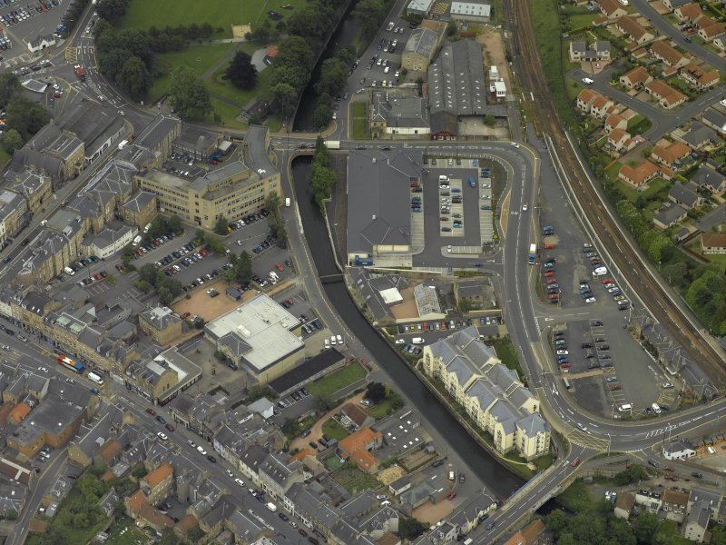 Oblique aerial view centred on the footbridge and railway station, taken from the NE.