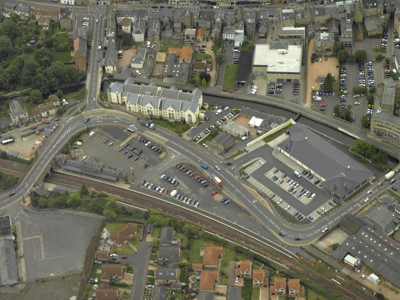 Oblique aerial view centred on footbridge and railway station, taken from the NW.