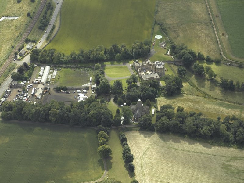 Oblique aerial view centred on the country house with the Collegiate Chapel adjacent, taken from the E.