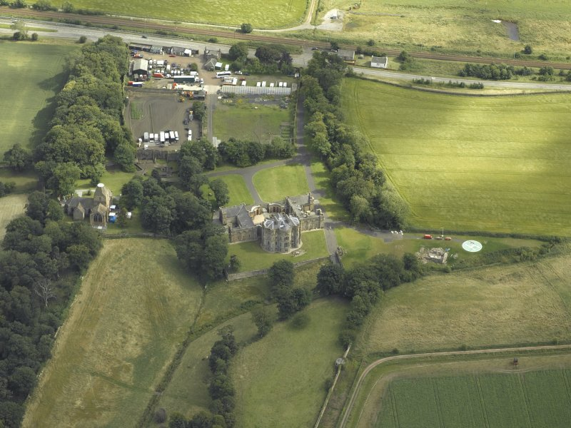 Oblique aerial view centred on the country house with the Collegiate Chapel adjacent, taken from the N.