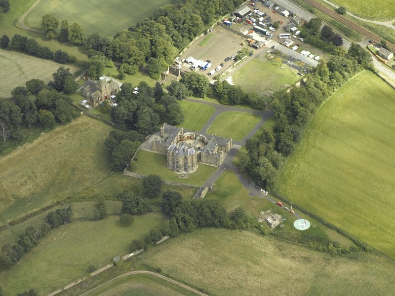 Oblique aerial view centred on the country house with the Collegiate Chapel adjacent, taken from the NW.