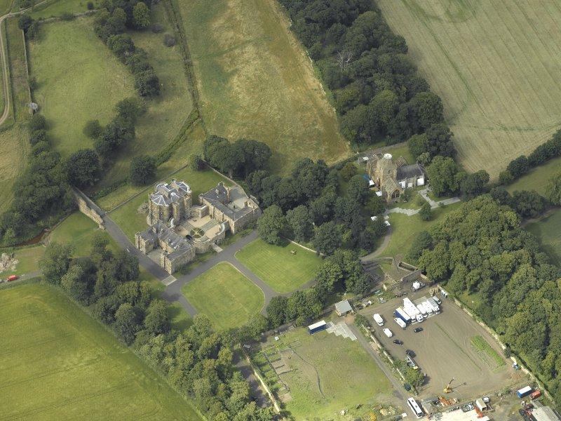 Oblique aerial view centred on the country house with the Collegiate Chapel adjacent, taken from the S.