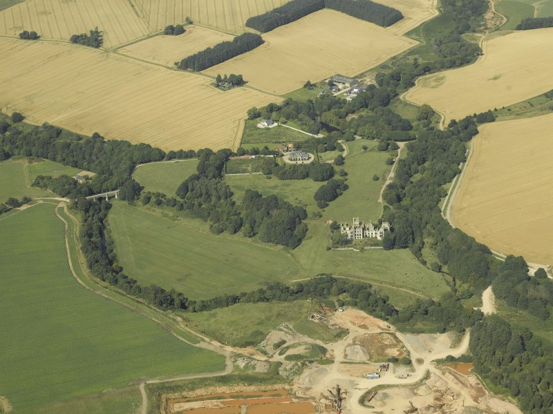 General oblique aerial view centred on the remains of Ury House with the sand and gravel pit in the foreground, taken from the NNE.
