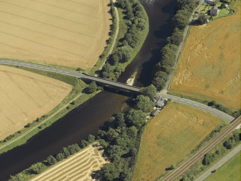 Oblique aerial view centred on the road bridge and the tollhouse, taken from the NW.