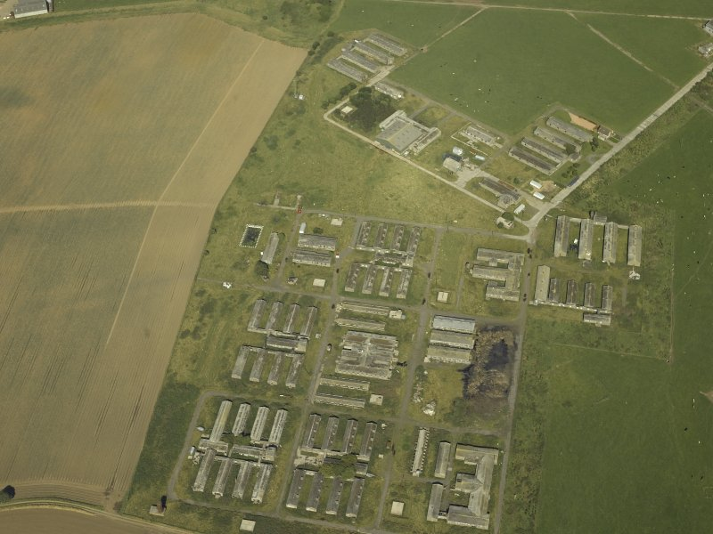 Oblique aerial view centred on the accommodation camp, taken from the SW.