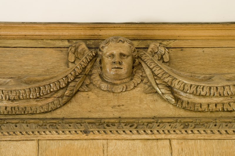 Interior.  Detail of carved wooden head on panelling in Ante-Room.