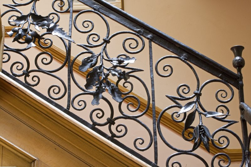 Interior.  Detail of staircase balustrade, thistle, oak and tulip motifs.
