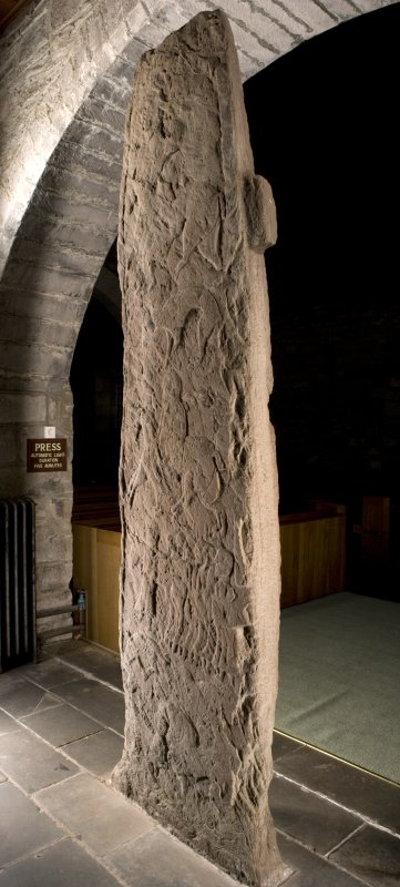Oblique view of cross slab showing rear face with carved figures and symbols