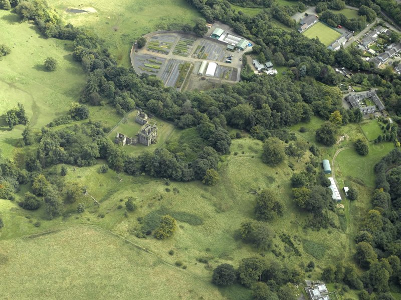 Oblique aerial view centred on the house and walled garden with the earthwork adjacent, taken from the NW.
