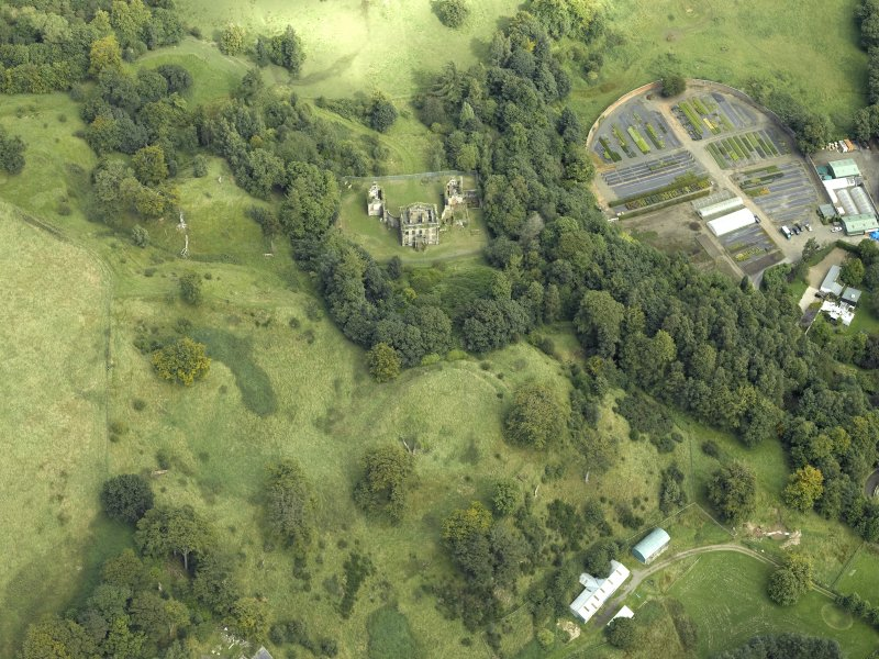 Oblique aerial view centred on the house and walled garden with the earthwork adjacent, taken from the SW.