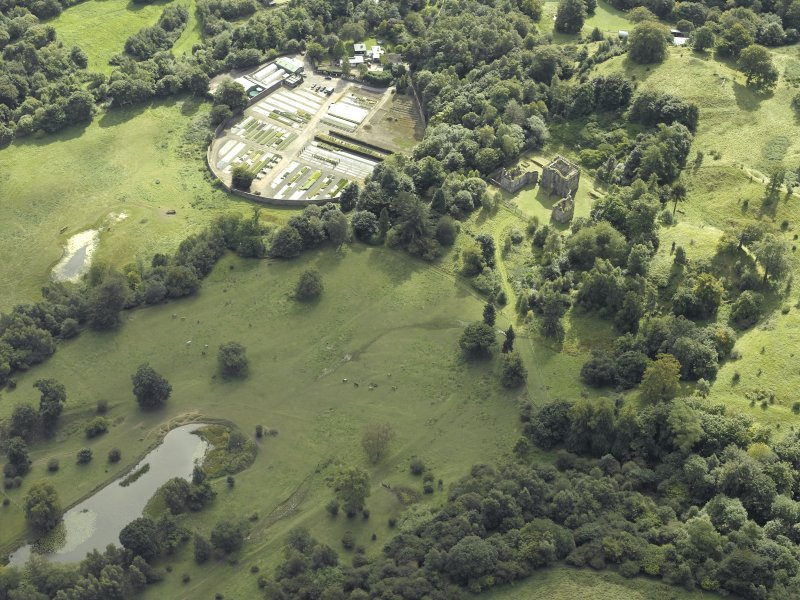 Oblique aerial view centred on the house and walled garden with the earthwork adjacent, taken from the N.