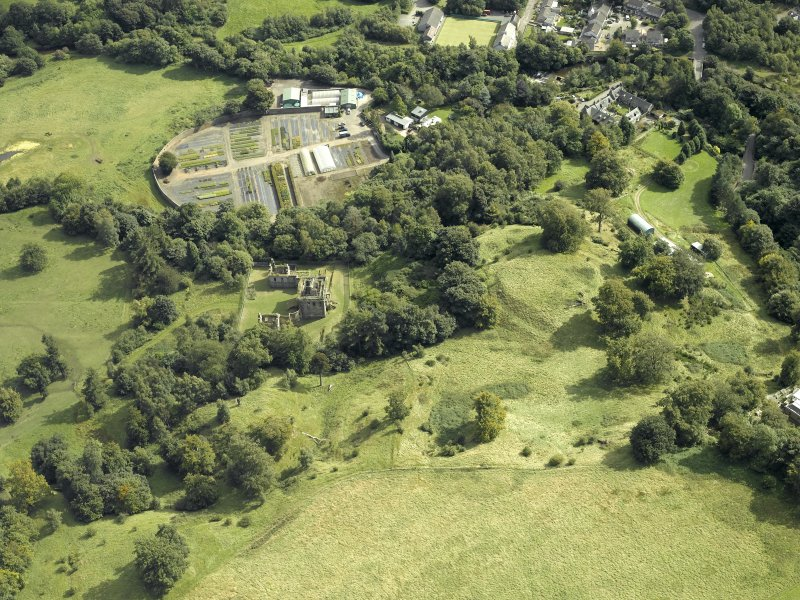 Oblique aerial view centred on the house and walled garden with the earthwork adjacent, taken from the NNW.