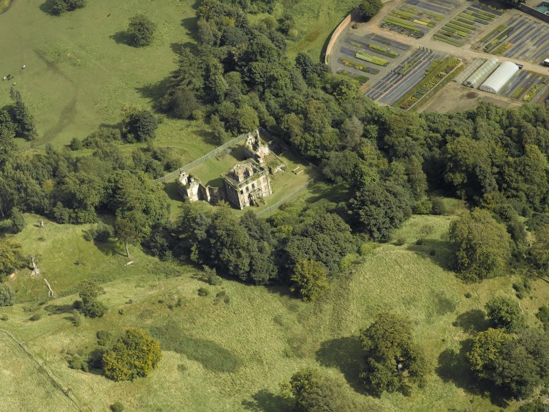 Oblique aerial view centred on the house and walled garden with the earthwork adjacent, taken from the W.