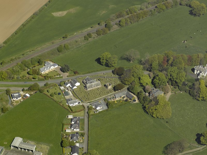 Oblique aerial view centred on the Church with the manse adjacent, taken from the SW.