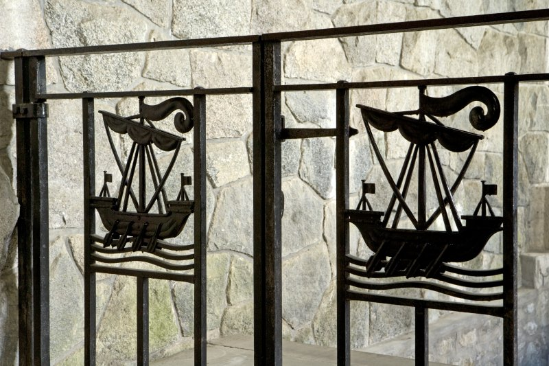 Interior. Detail of iron gates with ship motif at head of stair to undercroft.