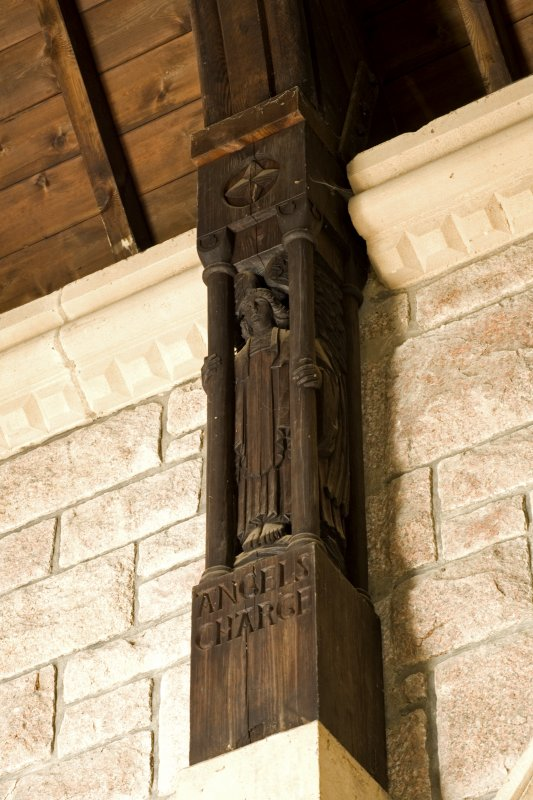 Interior. S aisle, detail of carved wooden pillar supporting roof