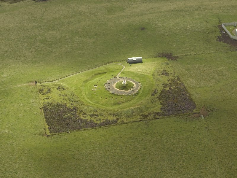 Oblique aerial view centred on the remains of henge and cairn, taken from the SW.