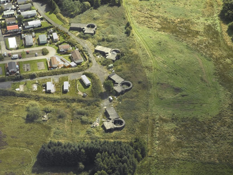 Oblique aerial view centred on the postwar anti-aircraft battery gun emplacements with the WW II radar ramp adjacent, taken from the NW.