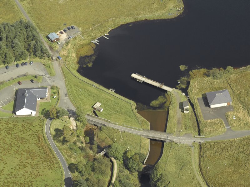 Oblique aerial view centred on the dam and sluice with bridge adjacent, taken from the W.
