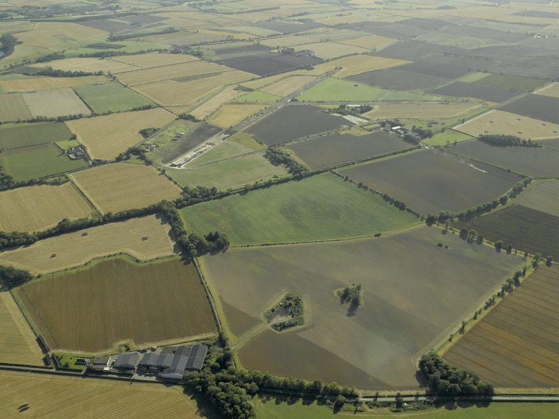 General oblique aerial view of the remains of the accommodation camp with the airfield adjacent, taken from the NE.