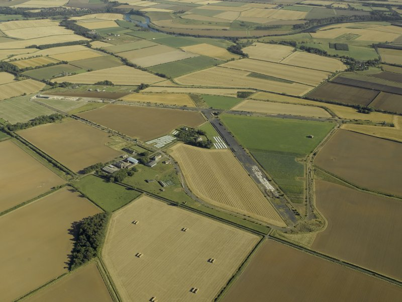General oblique aerial view of the airfield with the farmstead adjacent, taken from the NW.