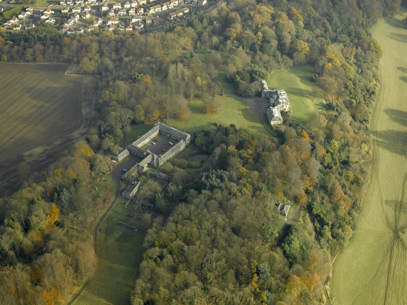Oblique aerial view centred on the house and stable block, taken from the W.