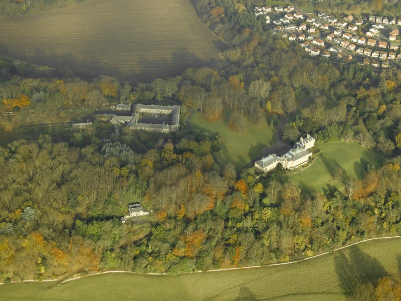 Oblique aerial view centred on the house and stable block, taken from the SSW.